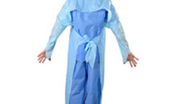 A doctor dressed in surgery clothes stands in an operating ...